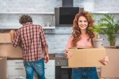 couple unpacking cardboard boxes at new home, girlfriend holding box with plant and looking at camera