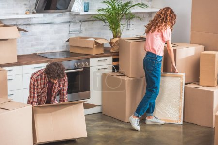 Photo for Couple with curly hair unpacking cardboard boxes at new home - Royalty Free Image