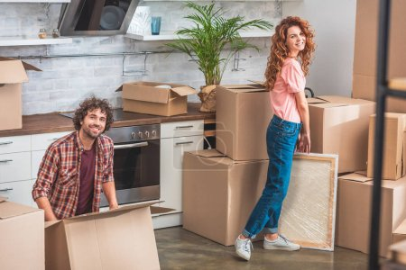 Photo for Smiling couple unpacking cardboard boxes at new home and looking at camera - Royalty Free Image