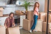smiling couple unpacking cardboard boxes at new home and looking at camera