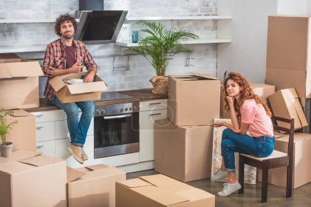 Photo for Couple unpacking cardboard boxes at new home and looking at camera - Royalty Free Image
