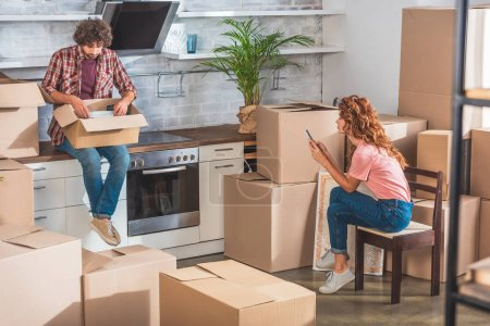 Photo for Boyfriend unpacking utensil from cardboard box at new home, girlfriend using smartphone - Royalty Free Image