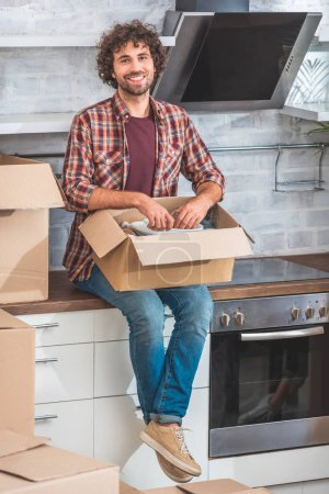 Photo for Handsome man sitting on kitchen counter and unpacking plates from cardboard box at new home - Royalty Free Image