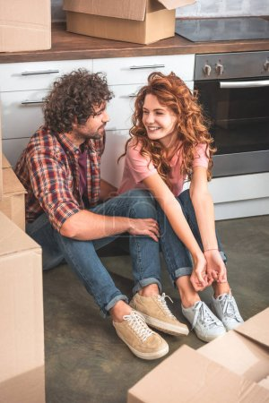 high angle view of cheerful couple sitting on floor near cardboard boxes in new kitchen and looking at each other