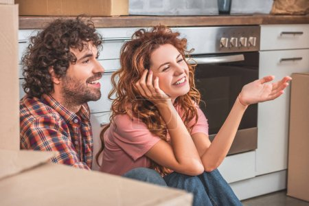 Photo for Smiling couple sitting on floor near cardboard boxes in new kitchen and looking away - Royalty Free Image