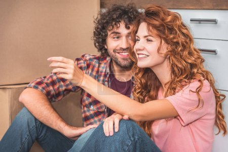 cheerful couple sitting on floor near cardboard boxes in new kitchen, girlfriend gesturing and looking away