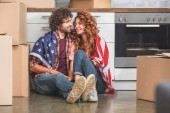 happy couple sitting wrapped in american flag near cardboard boxes at new home and looking at each other