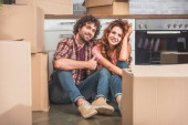 smiling couple sitting on floor near cardboard boxes in new kitchen, boyfriend showing thumb up