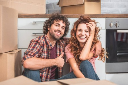 Photo for Happy couple sitting on floor near cardboard boxes in new kitchen, boyfriend showing thumb up - Royalty Free Image