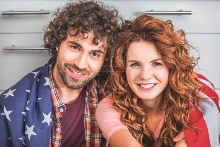 portrait of smiling couple sitting wrapped in american flag and looking at camera