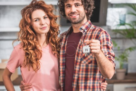 portrait of smiling couple hugging and holding house trinket with keys at new home