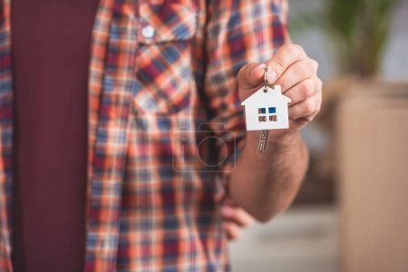 close-up partial view of man holding key from new house