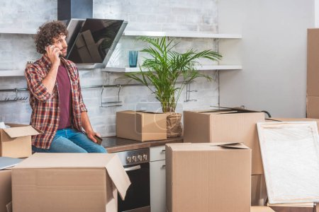 Photo for Young man talking by smartphone and looking away while sitting between cardboard boxes in new apartment - Royalty Free Image