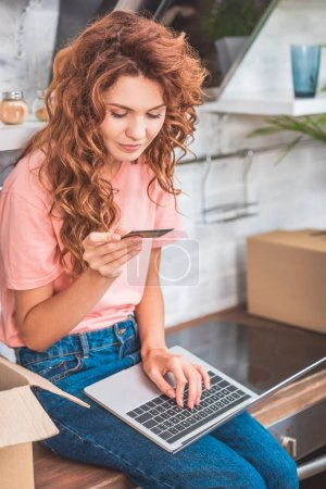 smiling young woman holding credit card and using laptop in new apartment