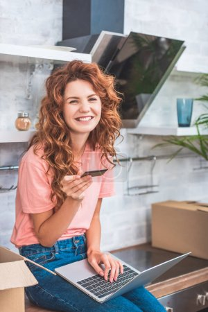 happy young woman holding credit card and using laptop in new apartment