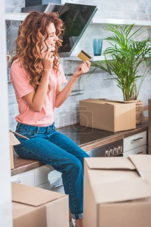 happy young woman holding credit card and talking by smartphone while relocating in new apartment