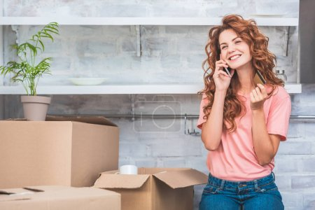 happy young woman holding credit card and talking by smartphone during relocation