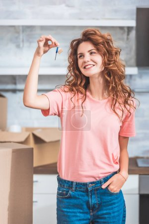 happy young woman holding key from new apartment