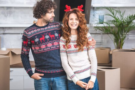 young man looking at smiling girlfriend in antlers headband while standing near cardboard boxes in new apartment
