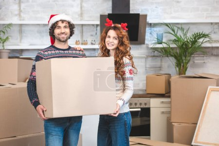 happy young couple holding cardboard box and smiling at camera while relocating in new home at christmastime