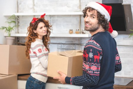 happy young couple unpacking cardboard boxes during relocation at christmastime