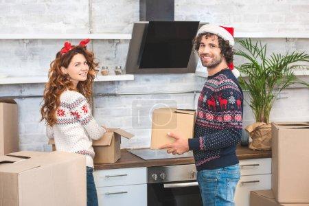 Foto de Feliz pareja joven desembalar cajas de cartón y sonriendo a la cámara mientras la reubicación en la nueva casa en Navidad - Imagen libre de derechos