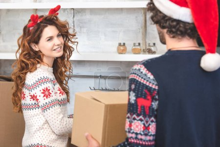young couple unpacking cardboard boxes during relocation at christmastime