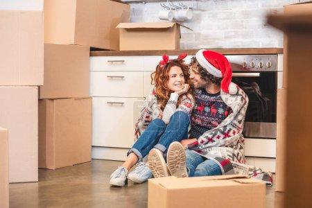 Foto de Feliz pareja joven sonriendo unos a otros mientras que se sentaba entre cajas de cartón en Navidad - Imagen libre de derechos
