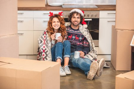 happy young couple holding cups and smiling at camera while sitting between cardboard boxes at christmastime