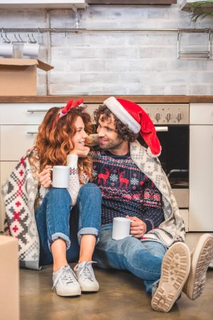 happy young couple holding cups and smiling each other while sitting in new home at christmas time