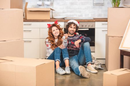 happy young couple holding keys and smiling at camera while sitting in new apartment at christmastime