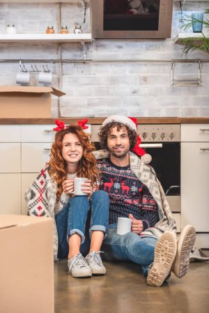 happy young couple holding cups and smiling at camera while sitting in new apartment at christmastime