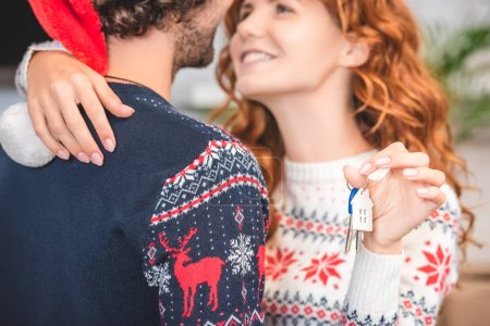 cropped shot of happy young couple hugging and holding keys from new apartment