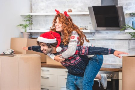 happy young couple having fun and smiling at camera while moving home at christmastime