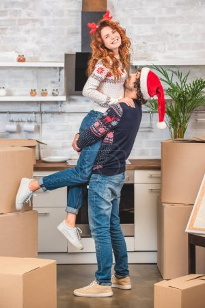 happy young couple hugging while relocating in new home at christmastime