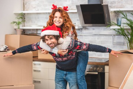 happy young couple having fun and smiling at camera while relocating at christmastime