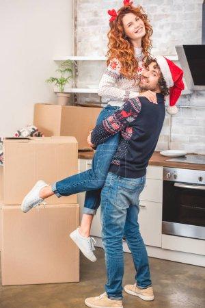 couple de jeunes heureux enlacements et souriant à la caméra tout en déplaçant à Noël