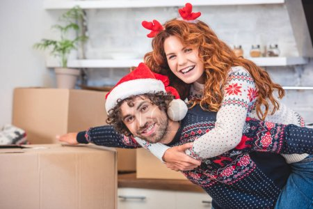 Photo for Happy young couple piggybacking and smiling at camera while relocating at christmastime - Royalty Free Image