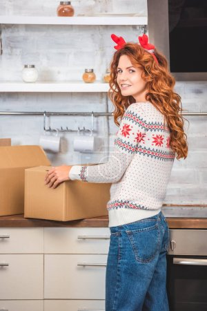 Photo for Beautiful young woman in antlers headband holding cardboard box and smiling at camera while relocating in new apartment - Royalty Free Image