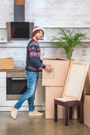 happy young man in santa hat holding cardboard box and smiling at camera while relocating in new apartment