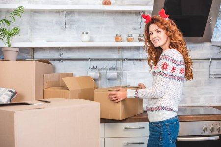 Photo for Happy young woman in antlers headband unpacking cardboard boxes and smiling at camera during relocation - Royalty Free Image