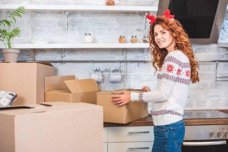 Foto de Mujer joven feliz en diadema cuernos desembalar cajas de cartón y sonriendo a la cámara durante la relocalización - Imagen libre de derechos
