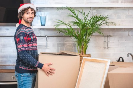 Photo for Handsome happy young man in santa hat holding cardboard box and smiling at camera during relocation - Royalty Free Image
