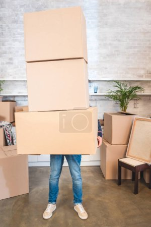 Photo for Young man holding cardboard boxes while moving home - Royalty Free Image