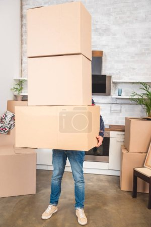 Photo for Man holding stack of cardboard boxes while moving home - Royalty Free Image