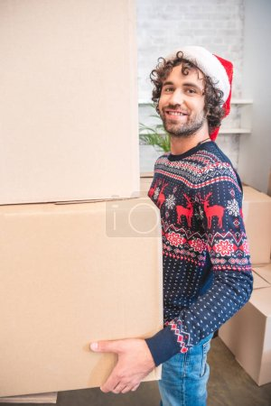 Photo for Happy young man in santa hat holding cardboard boxes and smiling at camera - Royalty Free Image