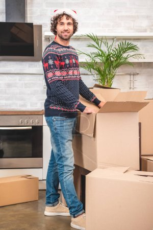 Photo for Handsome young man in santa hat unpacking cardboard boxes and smiling at camera - Royalty Free Image