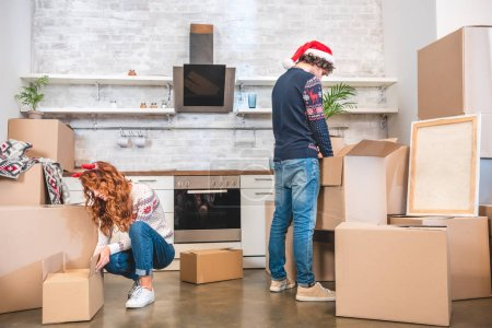young couple unpacking cardboard boxes in new apartment at christmastime