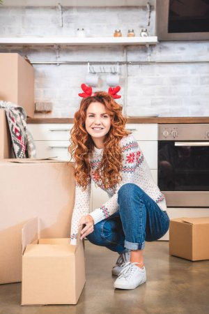happy young woman in antlers headband unpacking cardboard boxes and smiling at camera