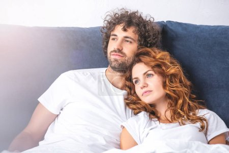 pensive young couple looking away while lying together in bed